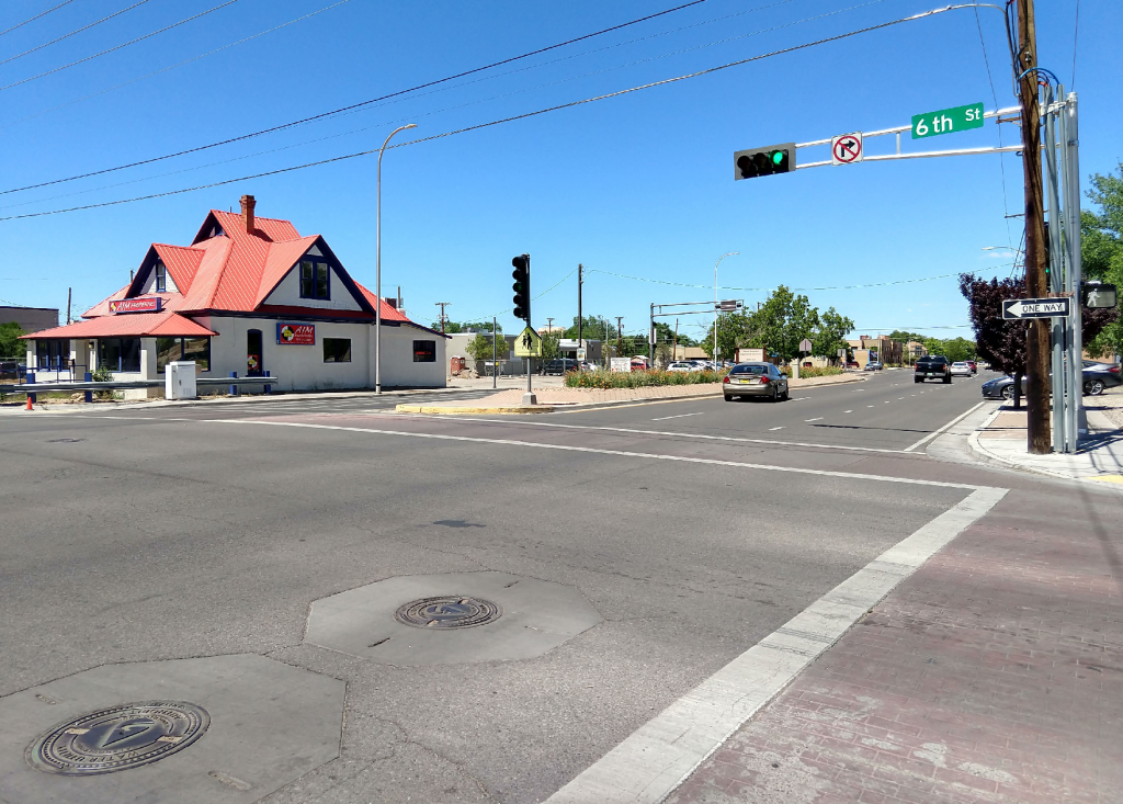 Existing conditions looking west on Lomas Boulevard. The existing curb ramps and sidewalks are narrow and do not allow those with disabilities to be visible while crossing the street.