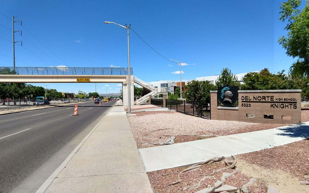 Existing conditions looking west on Montgomery Boulevard. The existing sidewalk is uncomfortable for pedestrians and the existing pedestrian bridge is not ADA-compliant and underused. The median fence is designed to discourage pedestrians crossing in this location.